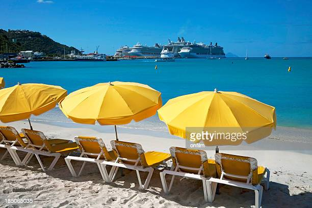 Sun loungers on beach with cruise ship in distance