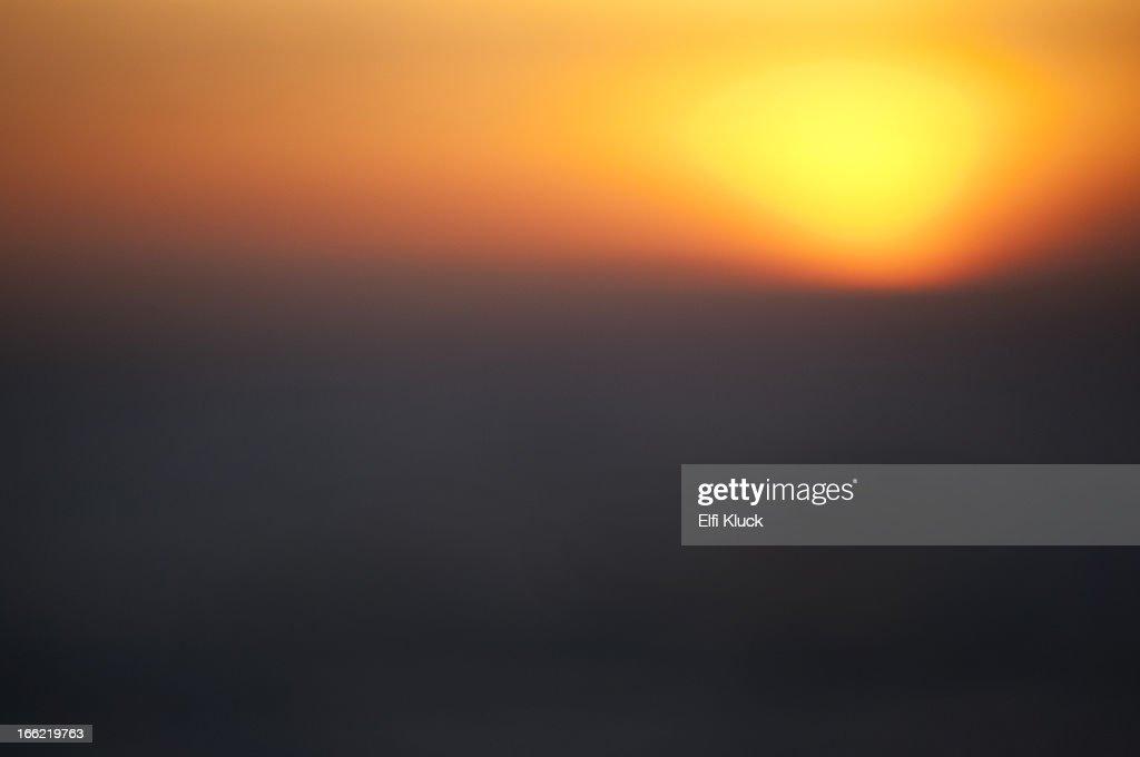 Sun melting into ocean : Stock Photo