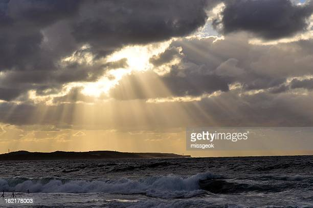 Sun Rays beaming through dark clouds over ocean
