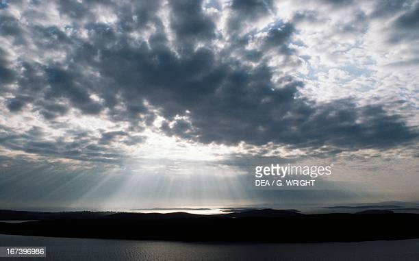 Sun rays filtering through clouds at sunset over Burra Islands Shetland Islands Scotland United Kingdom