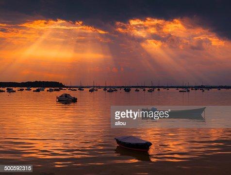 Sun rays illuminate boats in Poole Harbour : Stock Photo