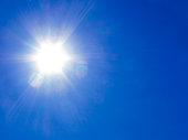 Glare from sun rays against clear blue sky.