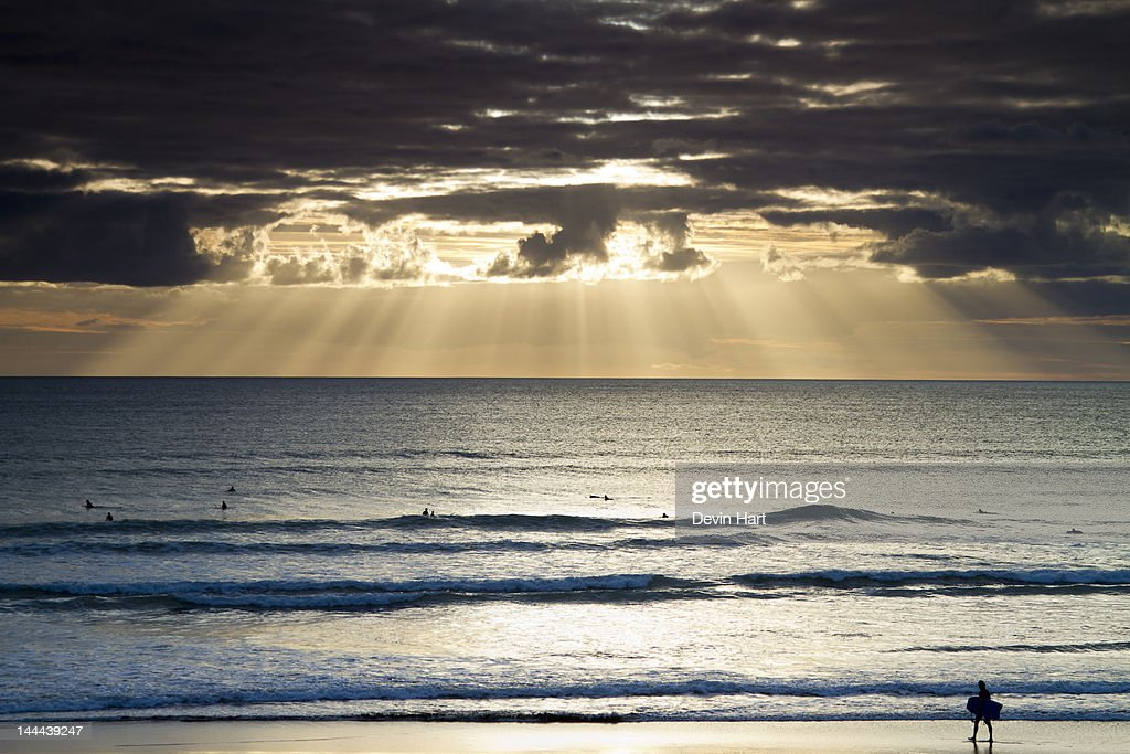 Sun rays over ocean and bodyboarder : Stock Photo
