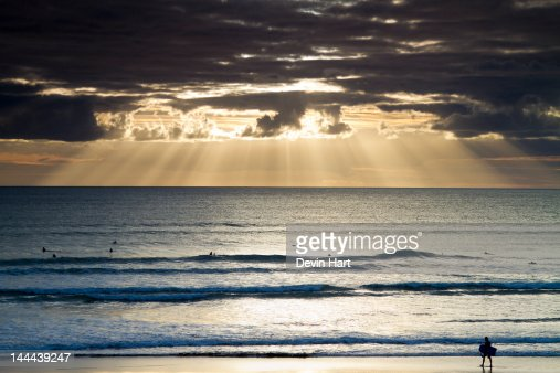 Sun rays over ocean and bodyboarder : Foto stock