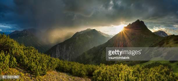 sun rays peaking behind a mountain ridge