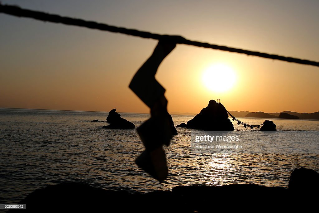 Sun rise between the 'Meoto-Iwa' or couple rocks and over the sea ahead of the Oshimenawahari ceremony at Futami Okitama Shrine on May 5, 2016 in Ise, Japan. The Oshimenawahari ceremony is held three times a year to exchange the 35 meters long heavy rope made of rice straw that connects the sacred Couple Rock - one small, one big. The Couple Rock serves as a gate to the Okitama Shrine, dedicated to the god Sarutahiko and goddess Ukanomitama from Japanese myth.