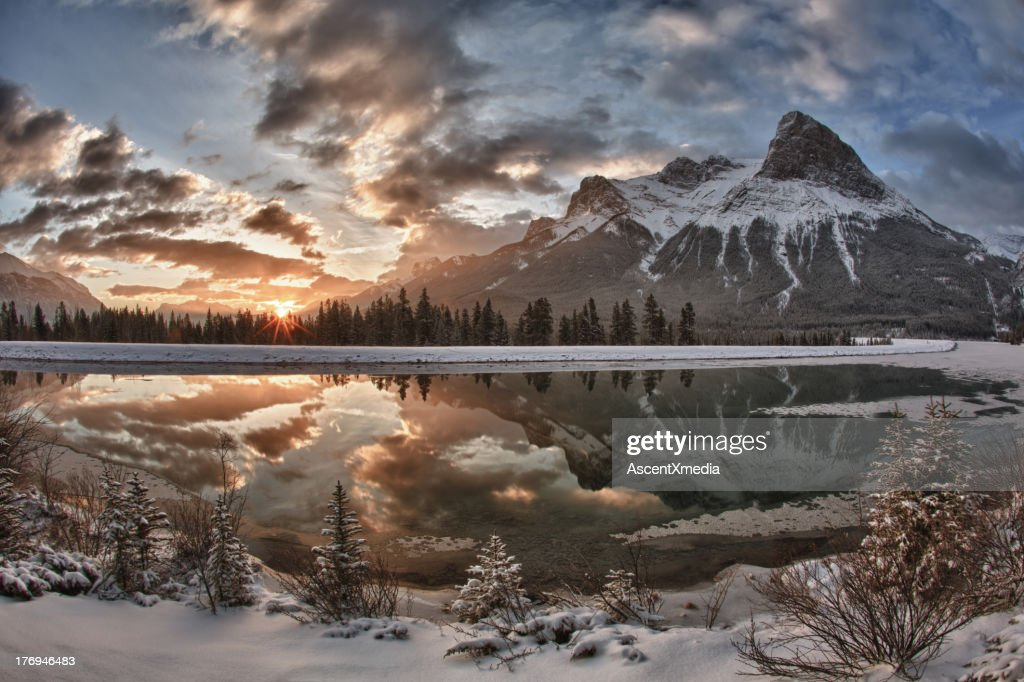 Sun rises above mountain lake, after snowfall : Stock Photo