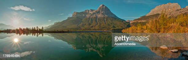 Sun rises above mountain lake, autumn