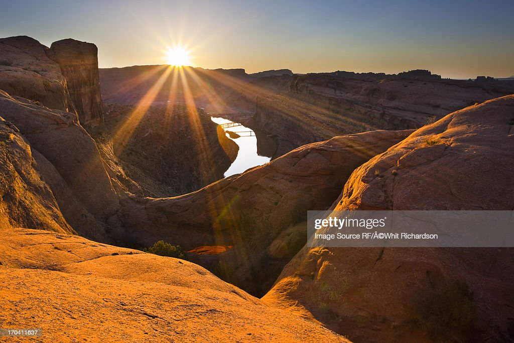 Sun rising over canyon rock formations : Stock Photo