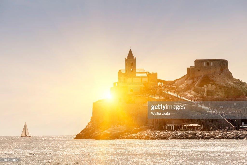 Sun rising over castle on island, Portovenere, Liguria, La Spezia, Italy