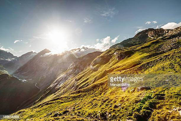Sun rising over grassy rural hillside