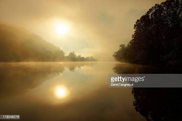 Sol a través de un creciente misty río James