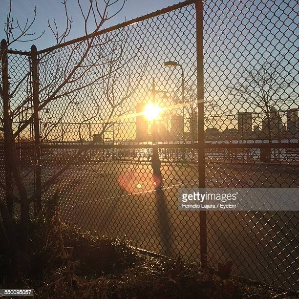 Sun Seen Through Chainlink Fence During Sunset