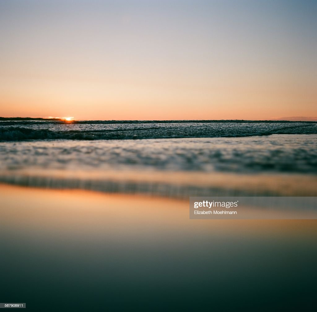sun sets on the horizon over Pacific Ocean