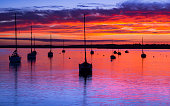 Deep colours emanate from the sunset, illuminating clouds and the calm seas of Poole Harbour at Rockley