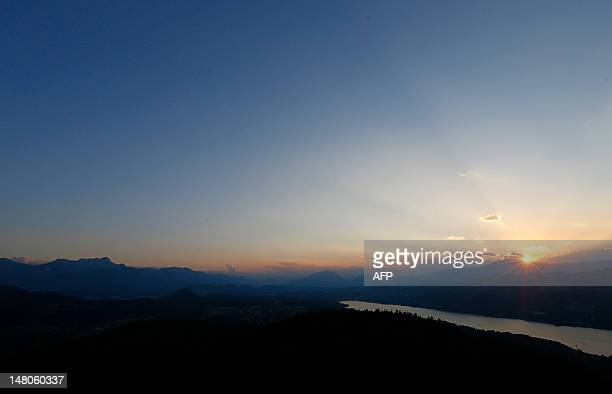 Sun sets over the mountains of Carinthia and the Worthersee lake in Hohe near Klagenfurt on July 8 2012 AFP PHOTO / ALEXANDER KLEIN