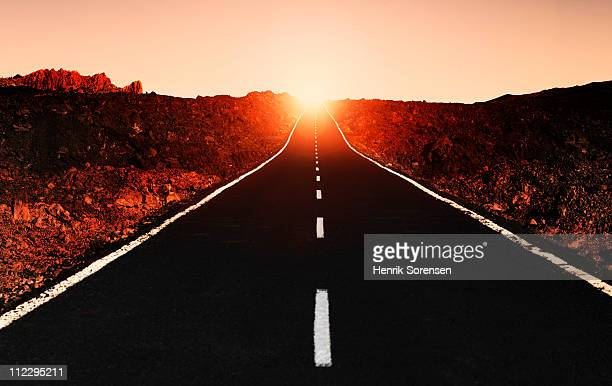 Sun setting behind a straight empty road