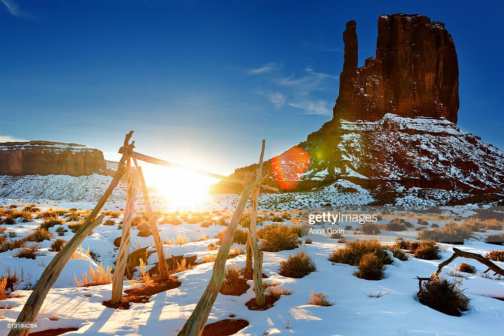 Sun setting under wooden structure by West Mitten along Wildcat Trail in Monument Valley, Utah, snowy winter evening