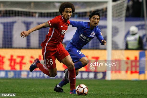 Sun Shilin of Shanghai Shenhua and Axel Witsel of Tianjin Quanjian compete for the ball during the 2nd round match of CSL Chinese Football...