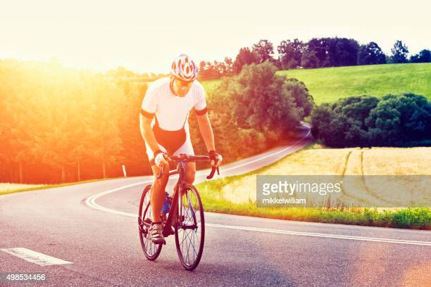 Sun shines on athlete who rides his bicycle up hill