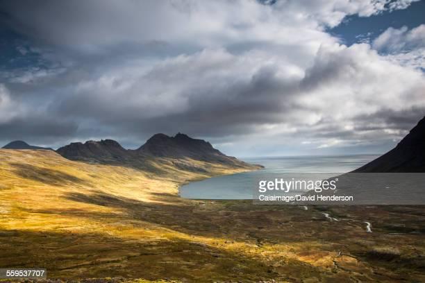 Sun shining along cliffs and shore, Veidileysa, West Fjords, Iceland