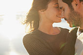 Sun shining behind couple hugging with eyes closed