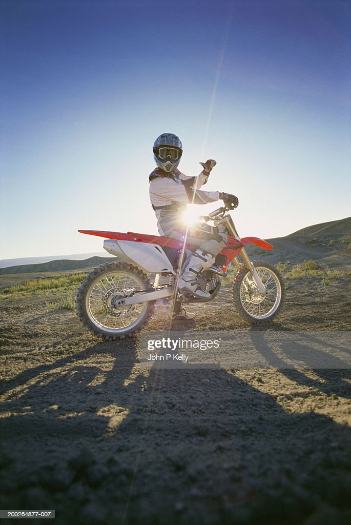 Sun shining behind motocross driver giving thumbs up, portrait : Stock Photo