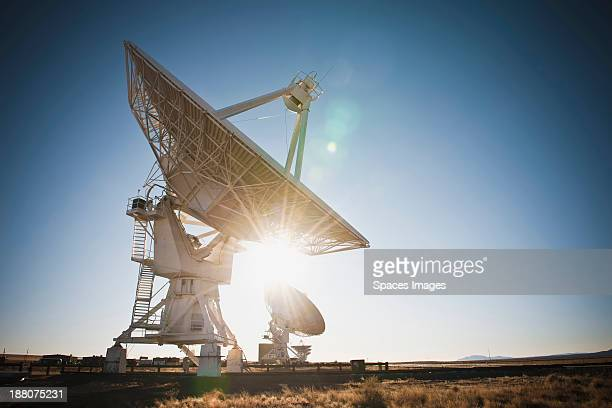 Sun shining behind satellite dish in desert, Socorro, New Mexico, United States