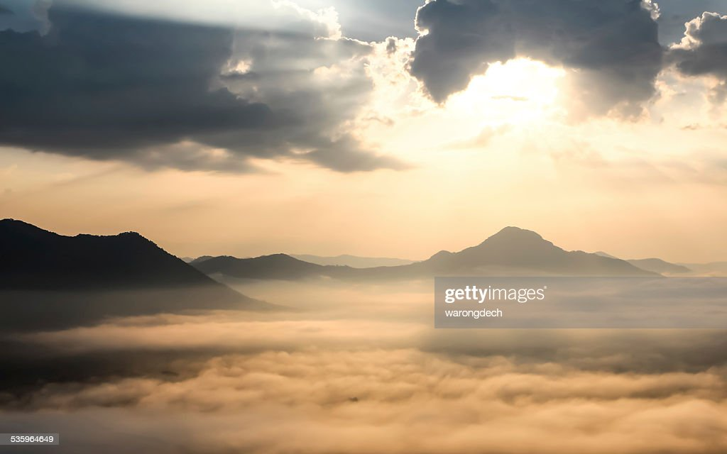 Sun shining behind the clouds on the mountain. : Stock Photo