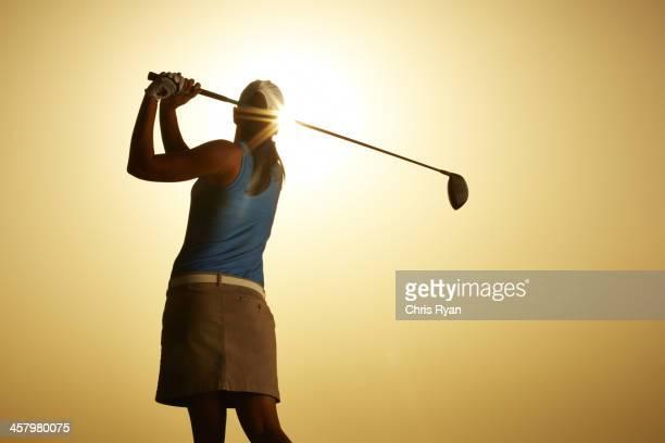 輝く太陽の下で女性スインギングゴルフクラブ