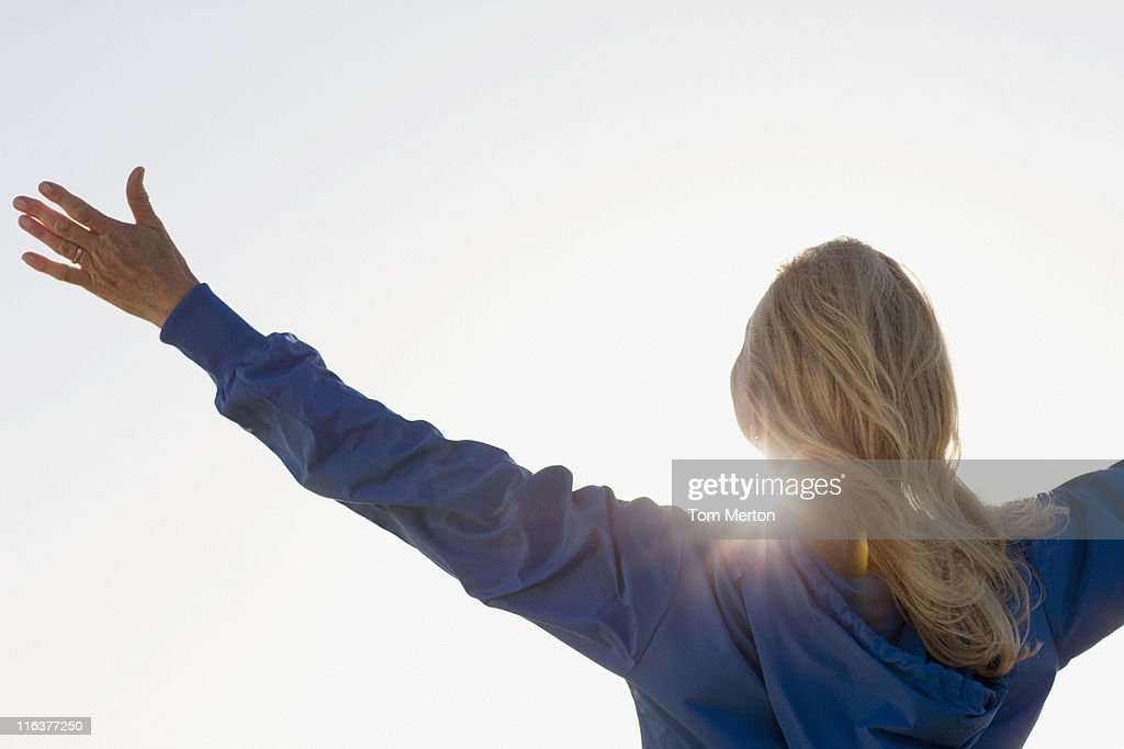 Sun shining behind woman with arms outstretched : Stock Photo