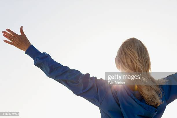 Sun shining behind woman with arms outstretched