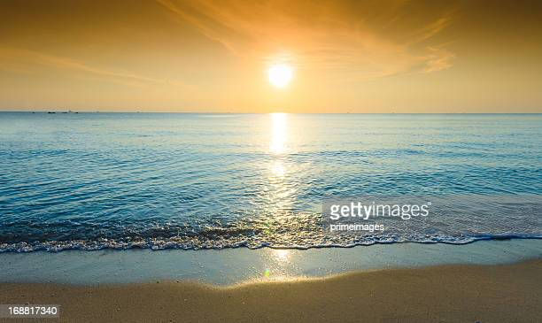 Sun shining brightly on rippling water and beach