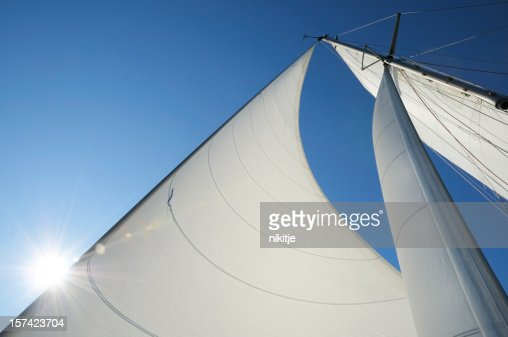 Sun shining from behind the sails of a yacht