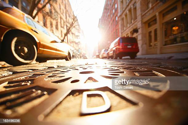 Sun shining manhole at SOHO stone pavement street.