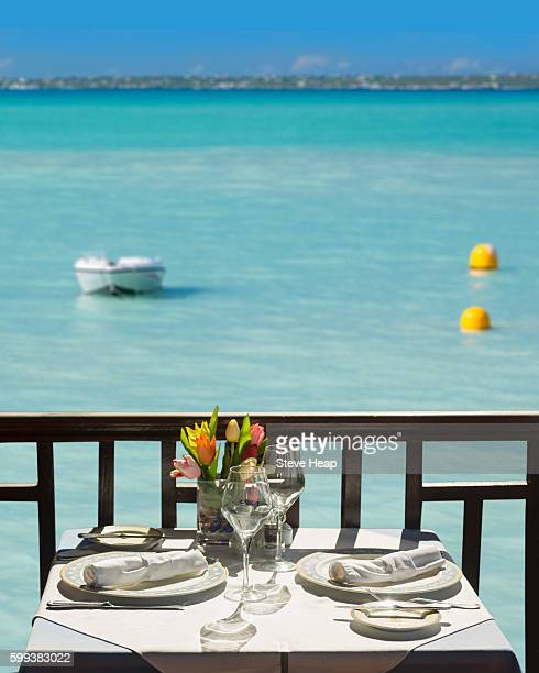 Sun shining on white tablecloth and table set for lunch in restaurant by beach of Grand Case on French side of St Martin in Caribbean