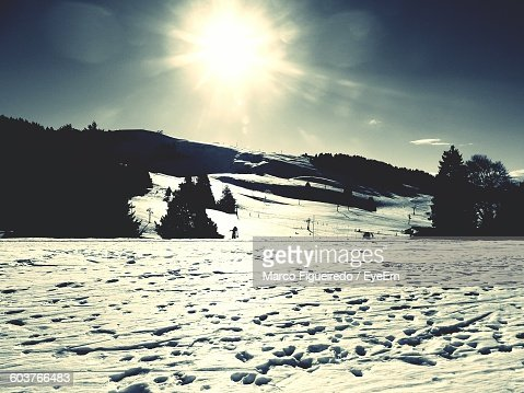 Sun Shining Over Snow Covered Landscape