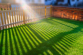 sunshine creating lens flare through a wooden picket fence in a front yard, front garden with artifical grass as a lawn and a red brick perimiter wall.