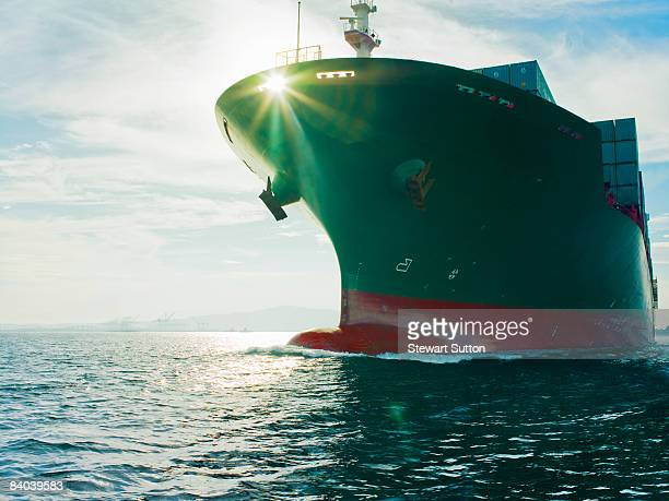 Sun shining through bow of cargo ship