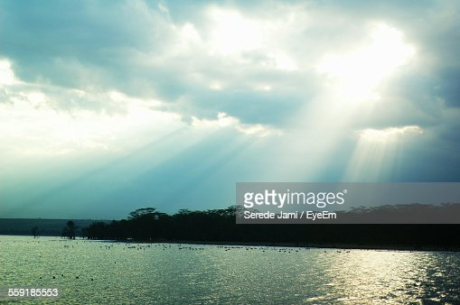 Sun Shining Through Clouds Over Lake