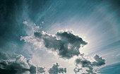 Sun shining through cumulus clouds