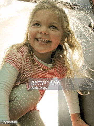 Sun shining through Girls hair on top of a Slide : Stock Photo