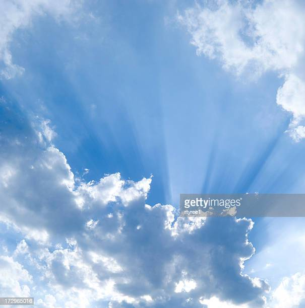 Sun shining through puffy clouds