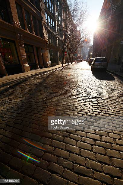 Sun shining to stone pavement street