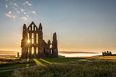 The Gothic ruins of Whitby Abbey with the suns rays producing a star.  Sea mist held back by the cliffs at Sandsend in the background