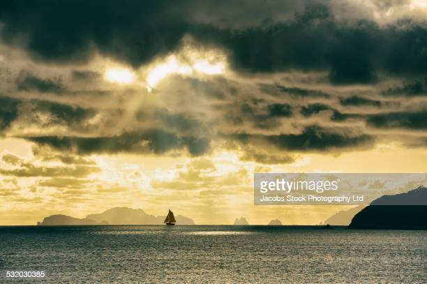 Sun streaming through dark storm clouds over sailboat on ocean