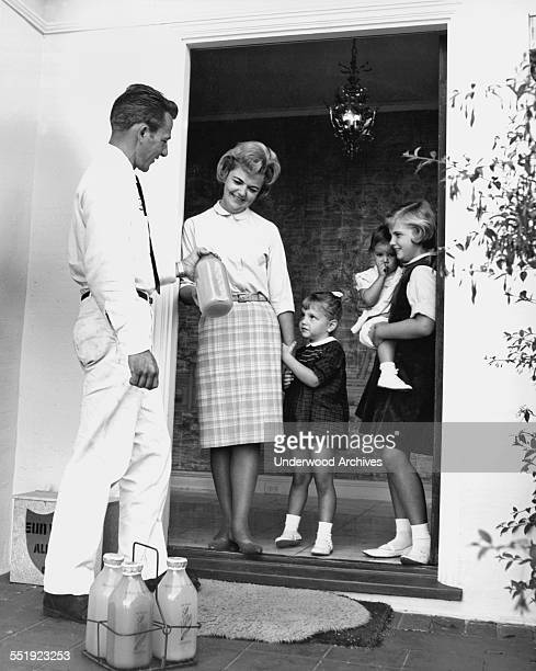 A Sun Valley Dairy milkman delivers half gallons of milk and lemonade in glass bottles to the home California circa 1955 The insulated box behind his...