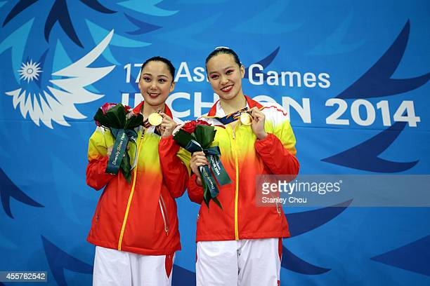 Sun Wenyan and Sun Yijing of China kisses their Gold Medals during the presentation ceremony of the Synchronised Swimming Duet Free Routine during...