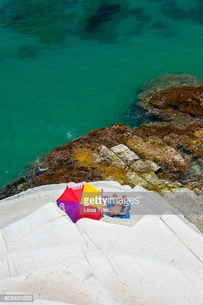 TURCHI REALMONTE SICILY ITALY A sunbaker at Scala dei Turchi or Stairs of the Turks at Realmonte southern Sicily Italy The Scala is formed by marl a...