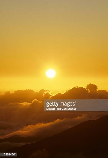 Sunball above cloudy mountaintop in yellow sunset sky.